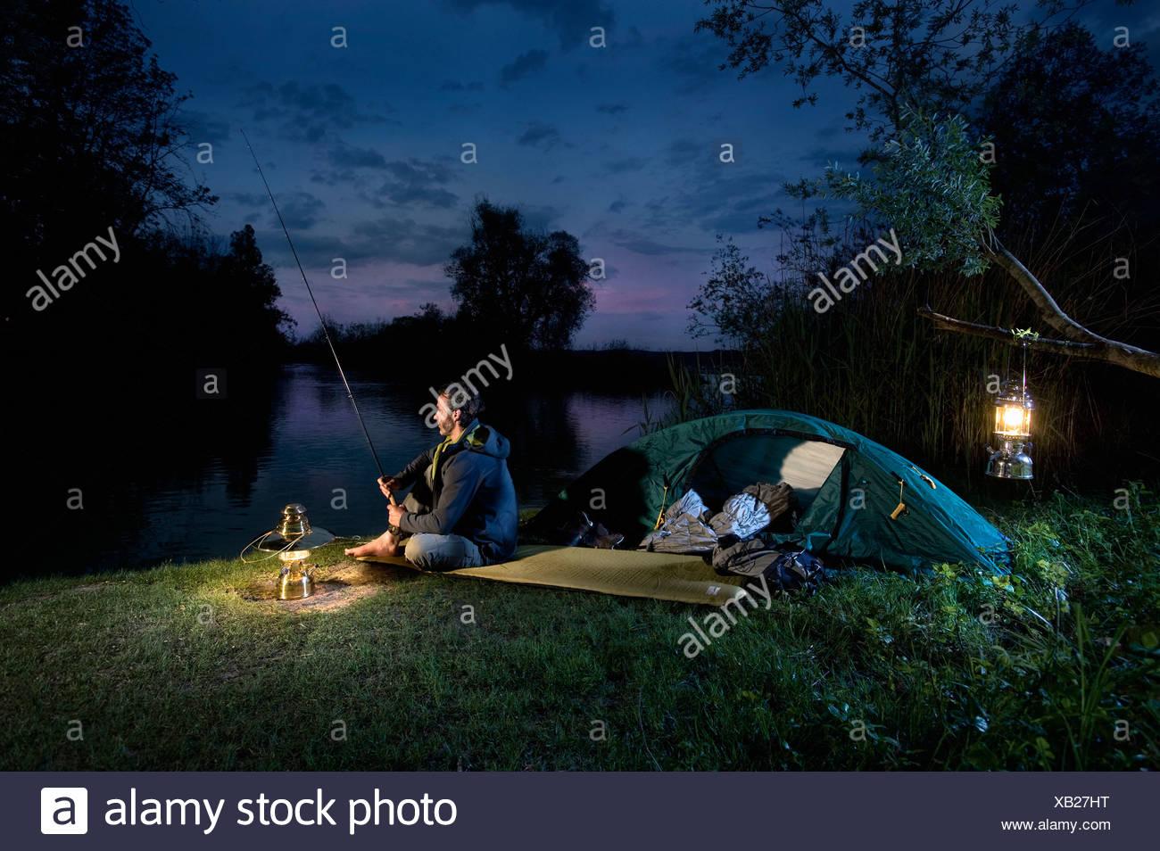 Germany, Bavaria, Ammersee, Man sitting near lakeshore with lantern and fishing at dusk - Stock Image