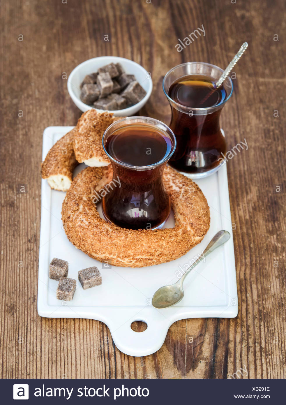 Turkish traditional black tea in a glass and turkish bagel simit on white ceramic serving board over wooden background selectiv - Stock Image