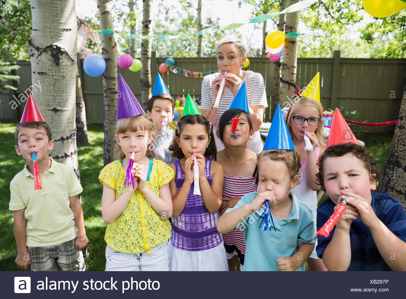 Portrait woman kids party hats blowing party favors - Stock Image