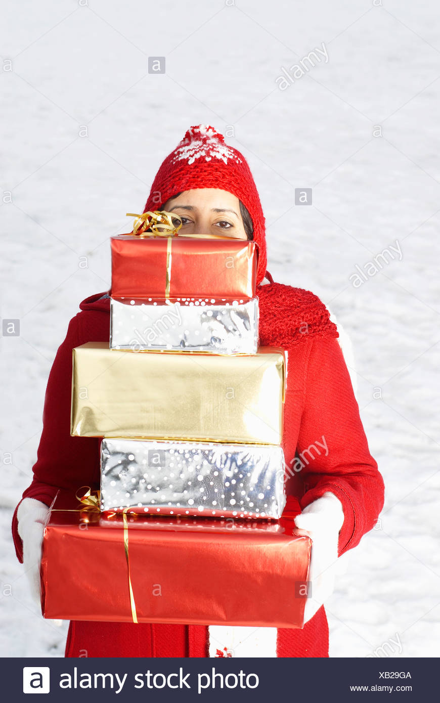 Girl carrying presents in snow Stock Photo