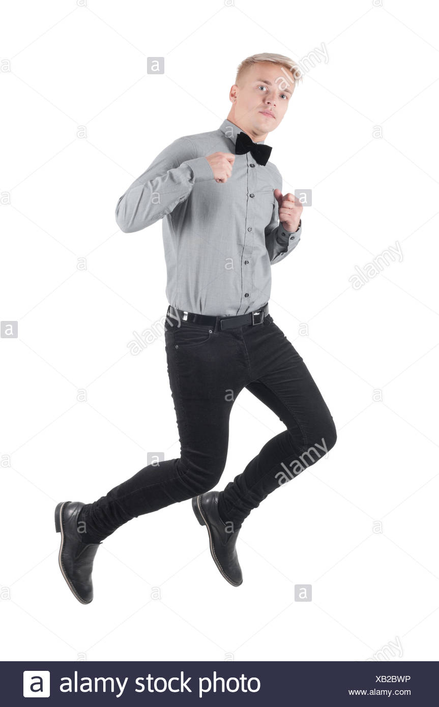 Handsome man in shirt and bow-tie jumping - Stock Image