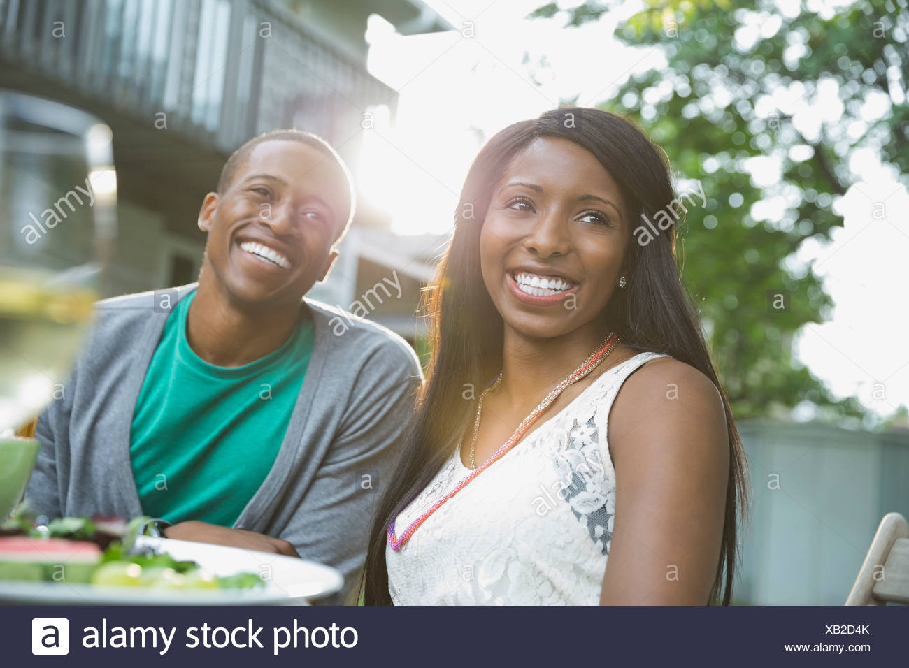 Cheerful couple sitting at outdoor dining table - Stock Image