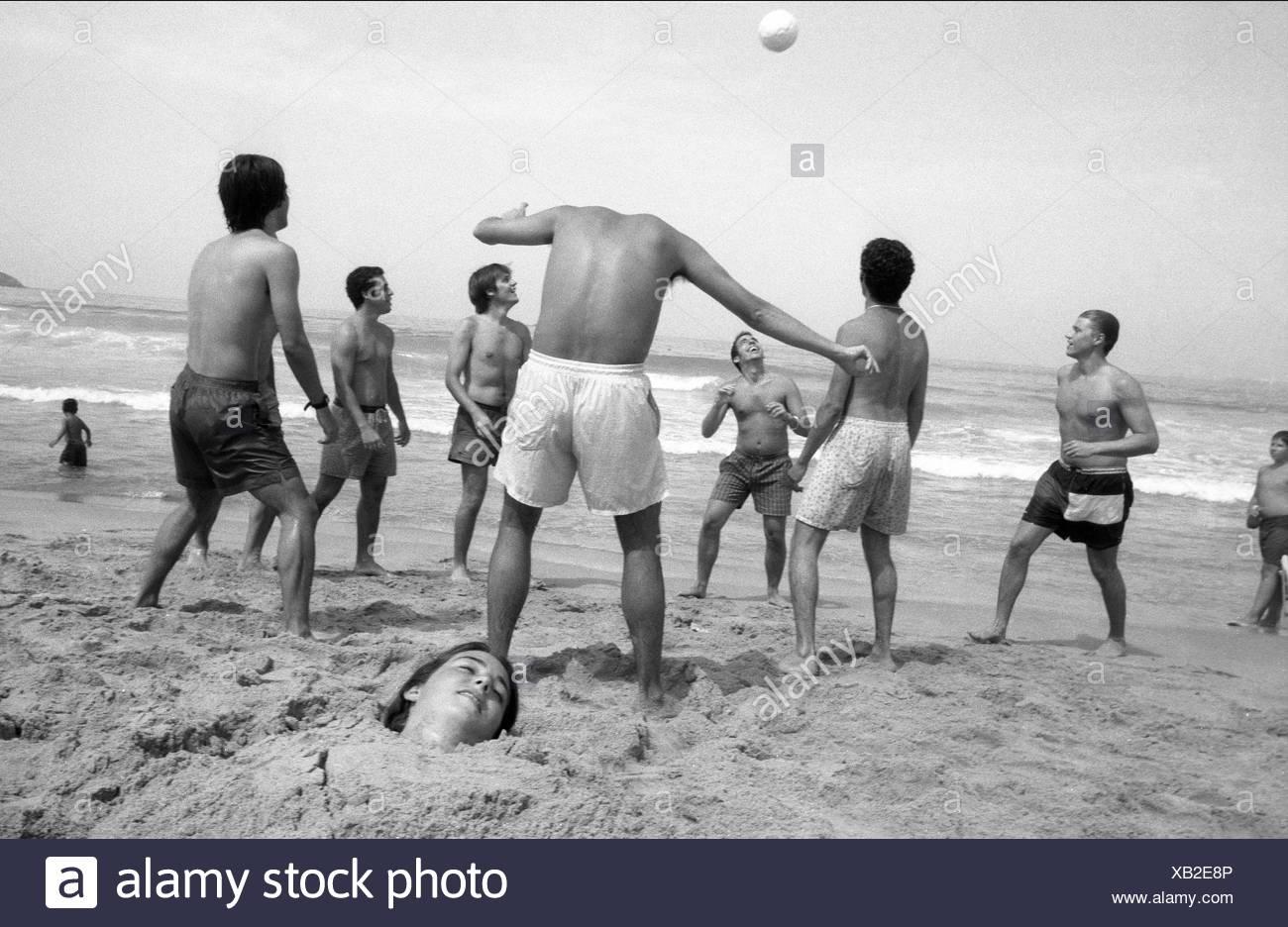 A headless man playing soccer on Algeciras beach. - Stock Image