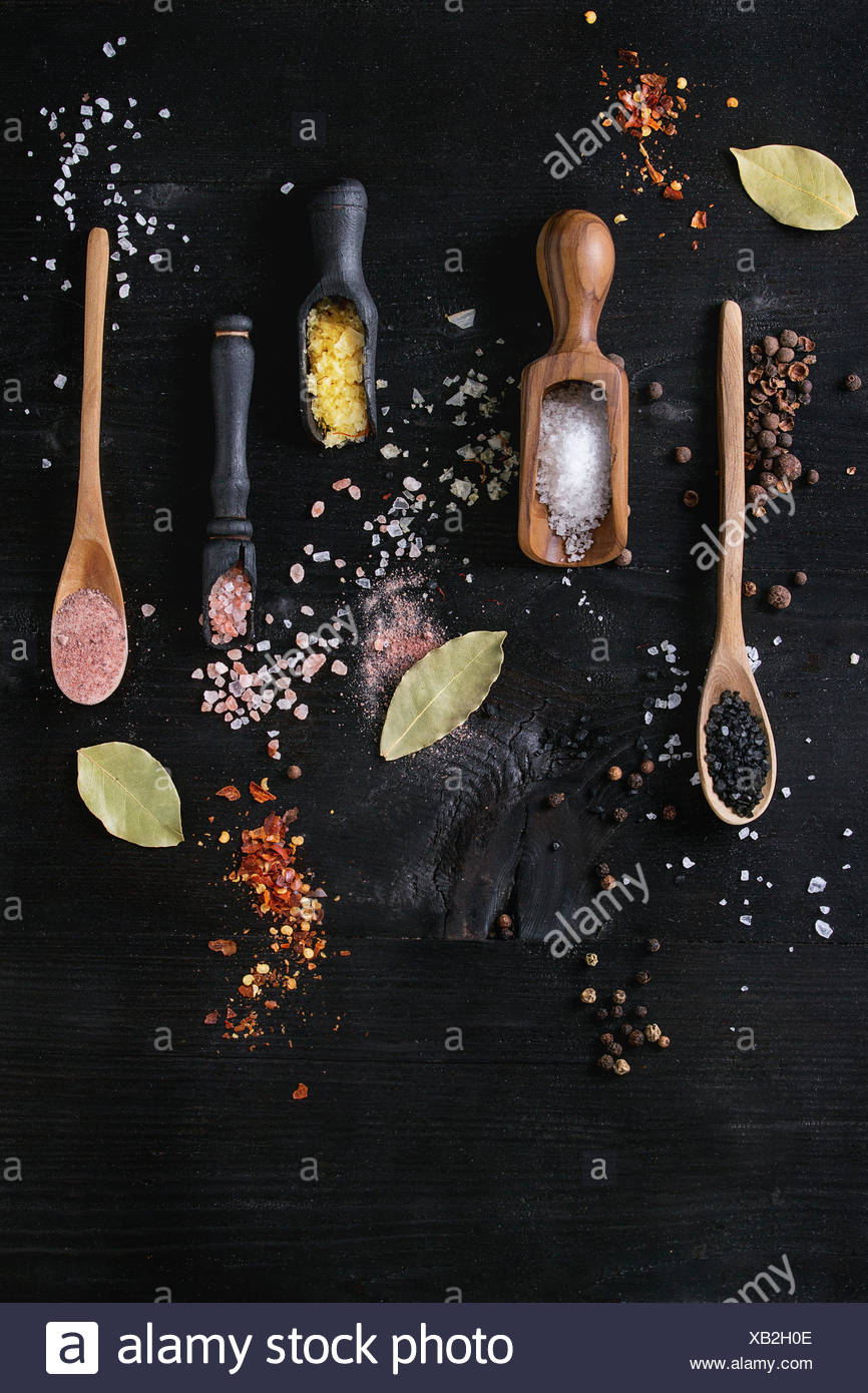 Variety of different colorful salt yellow saffron, pink, black himalayan, white sea and fleur de sel in wooden spoons with black, chili, allspice pepp - Stock Image