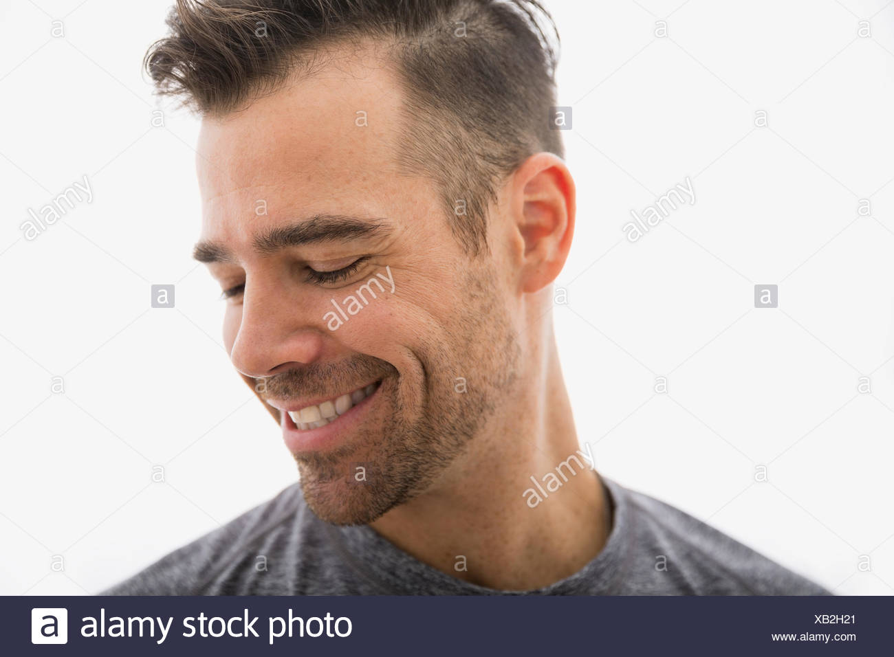 Close up of smiling brunette man looking down - Stock Image