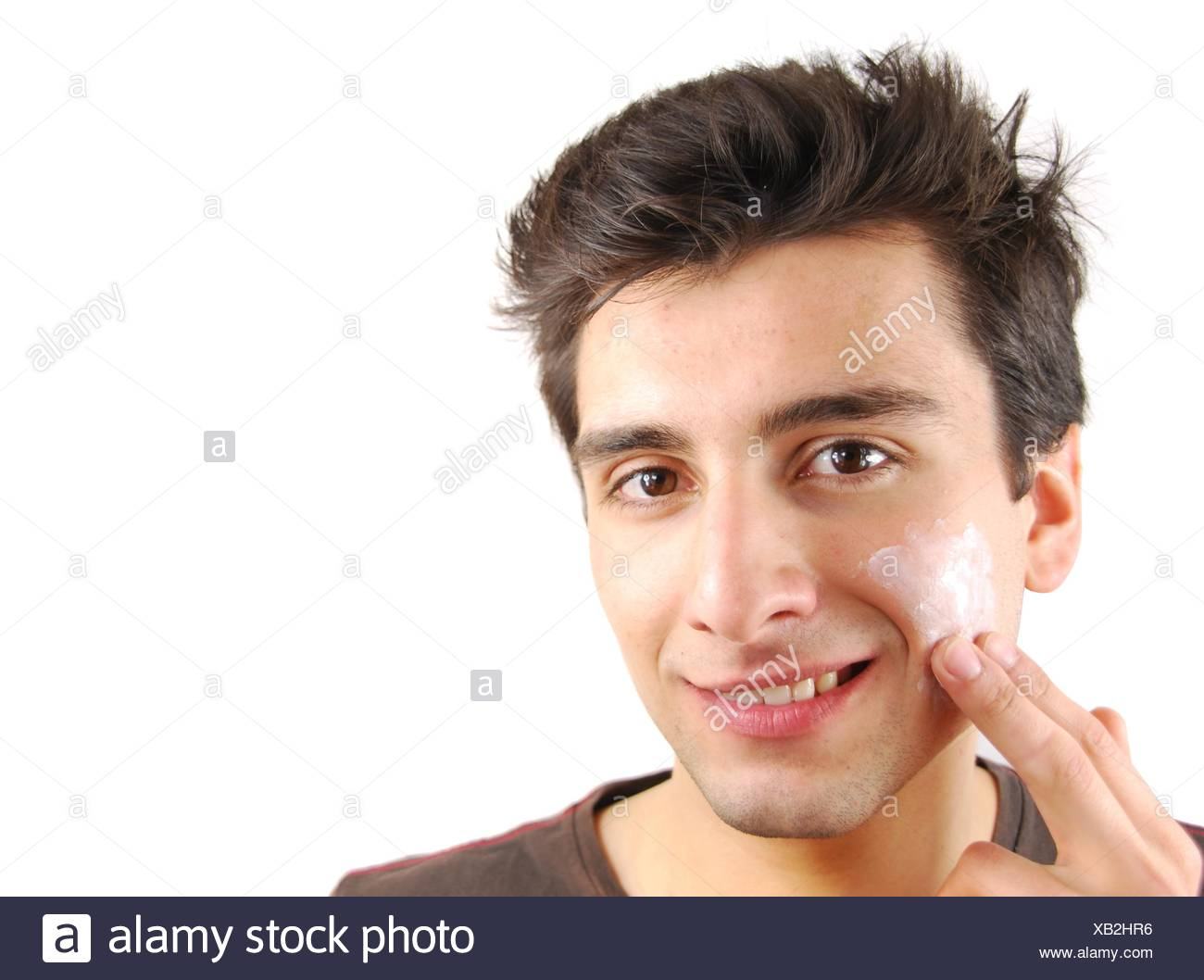 young handsome man applying face cream (over white background) - Stock Image
