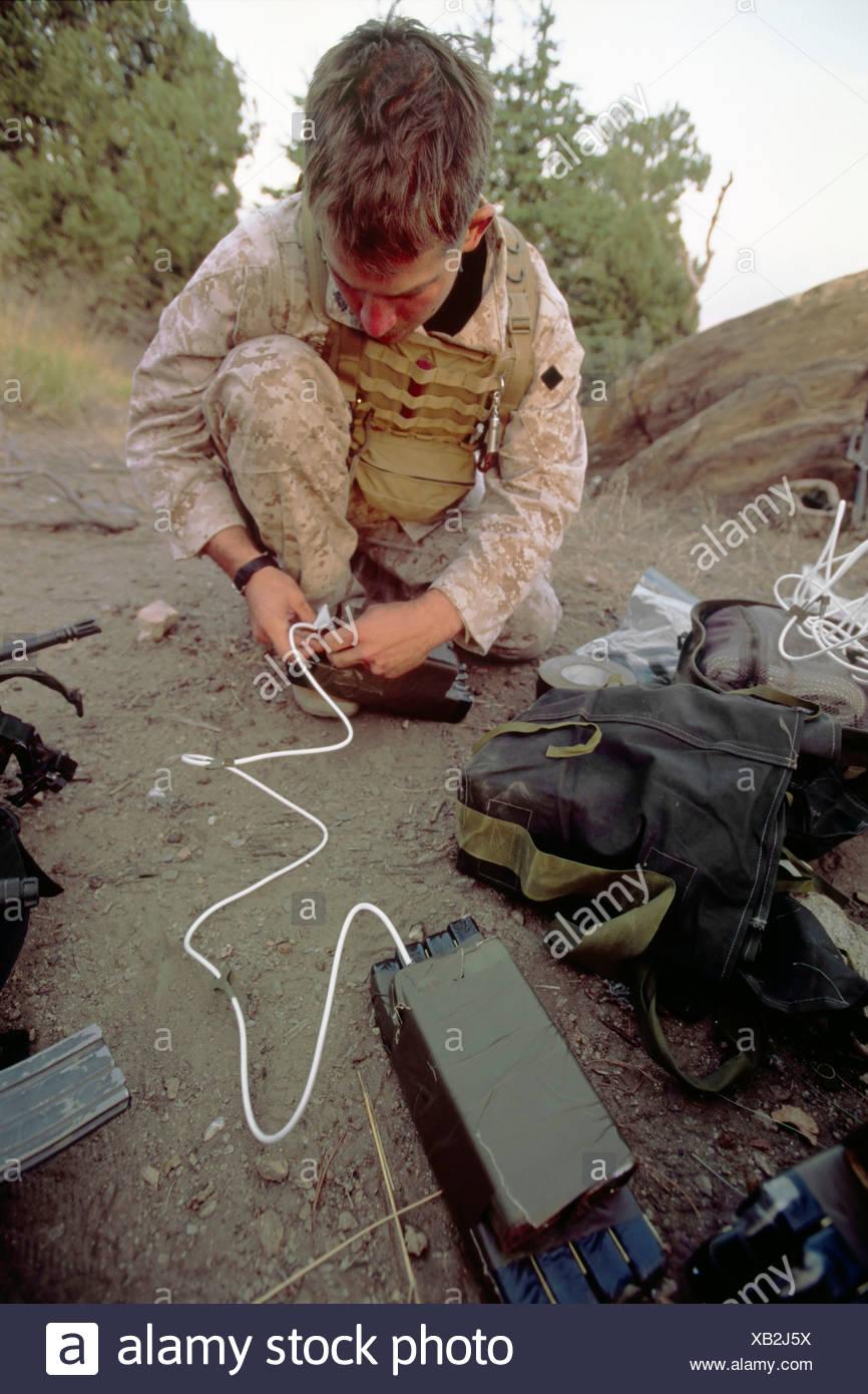 A US Marine Explosives Expert Prepares Composition 4 Explosives to Detonate a Discovered Al Qaeda Cave - Stock Image