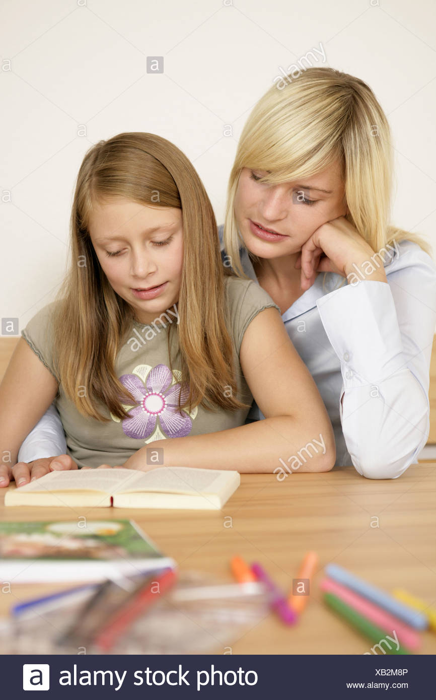 Mother taking homework of daughter Stock Photo