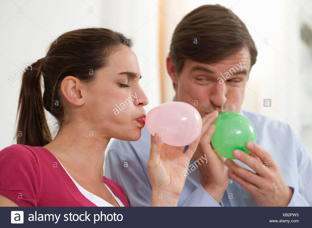 a couple trying to blow balloons - Stock Image