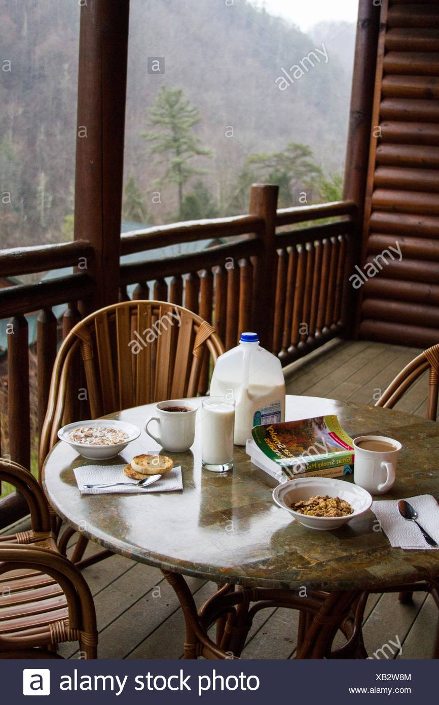 Breakfast table set with milk and cereals on the wooded balcony of a ski resort. The view from the mountains is incredible. - Stock Image