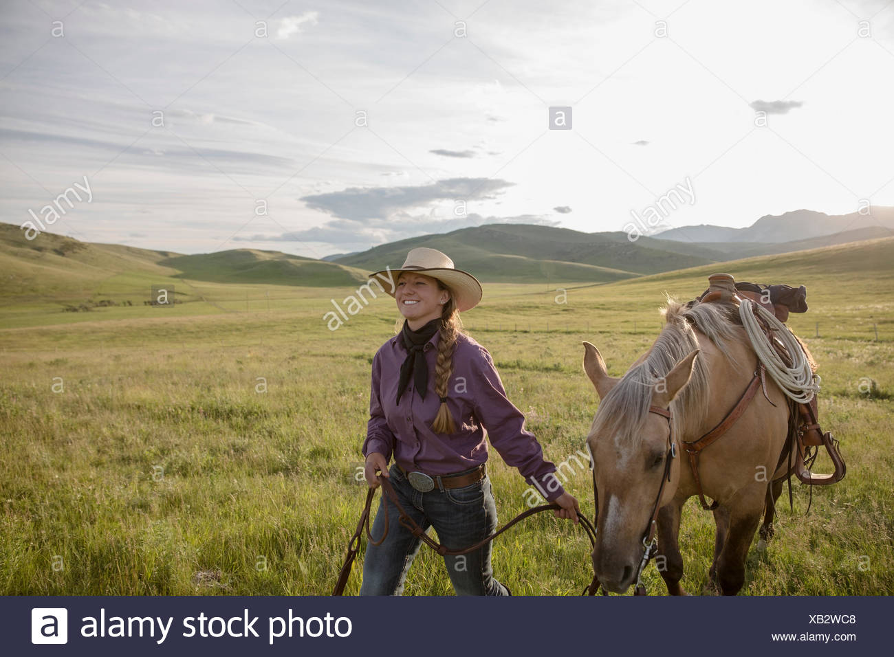Smiling female rancher walking horse sunny remote field - Stock Image