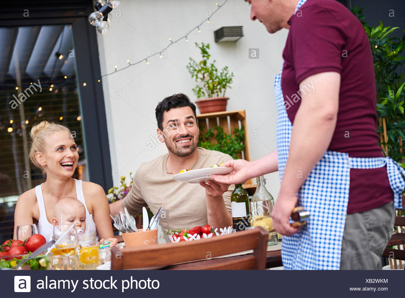 Man handing plate to couple with baby daughter at family lunch on patio - Stock Image