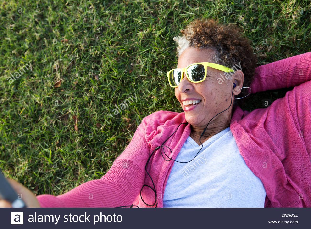 Portrait of senior woman lying on grass wearing sunglasses Stock Photo