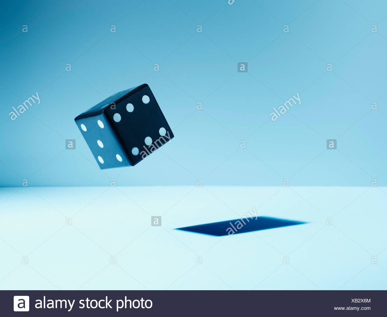 Black die in mid-air Stock Photo