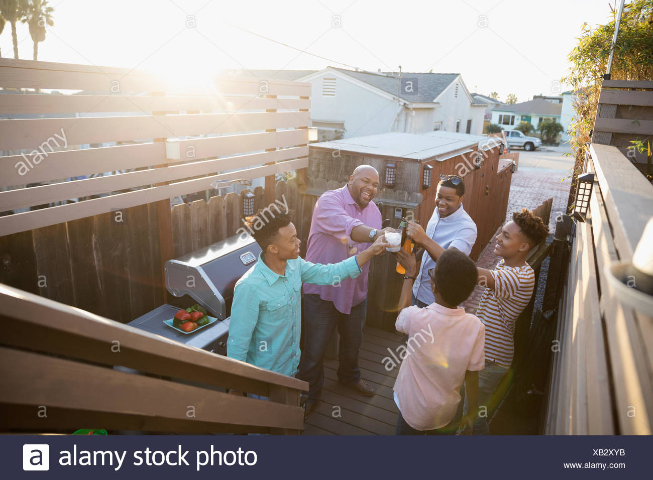 African American family toasting beer and soda, barbecuing on summer deck - Stock Image