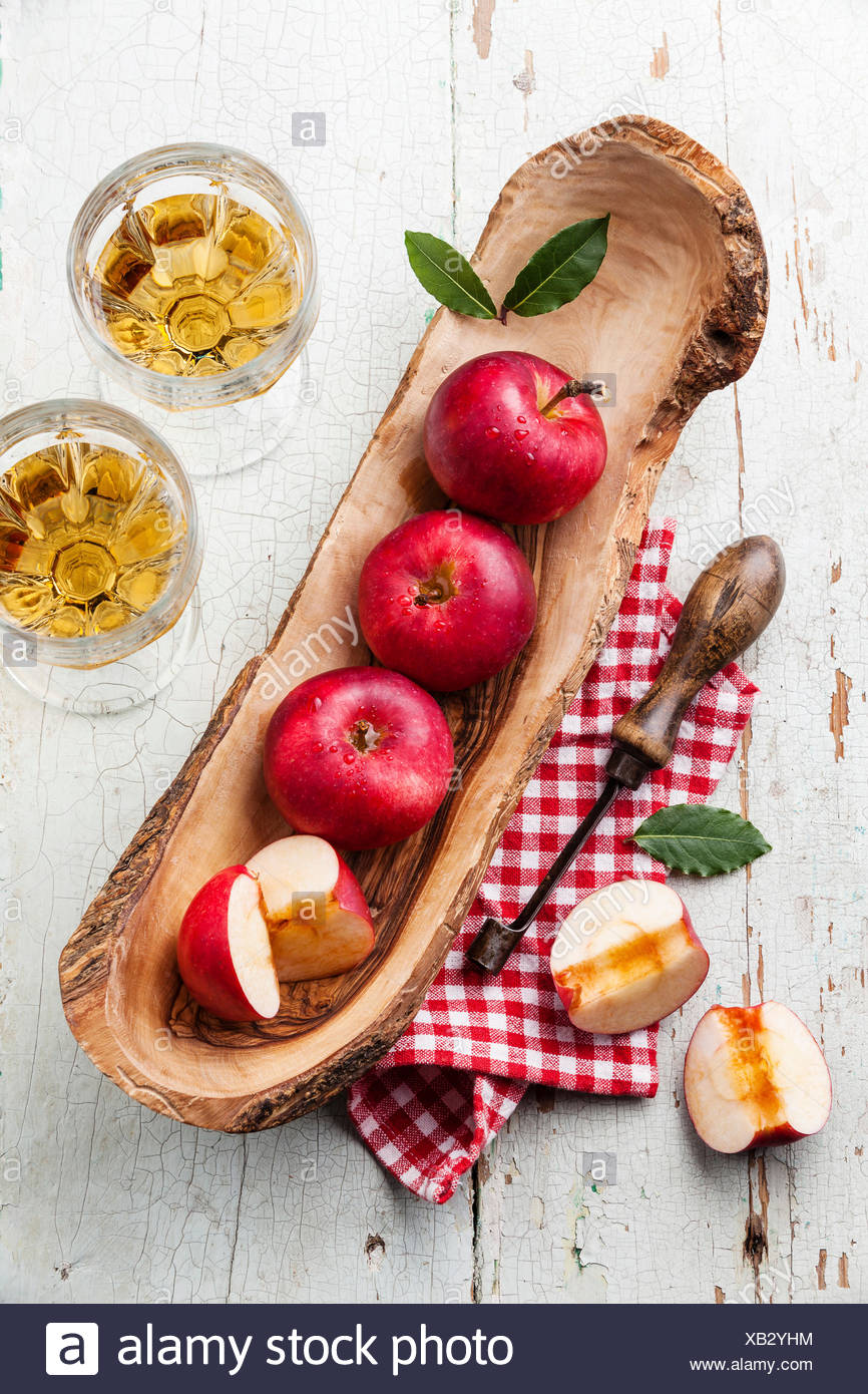 Red ripe apples in olive wood bowl and vintage core remover - Stock Image