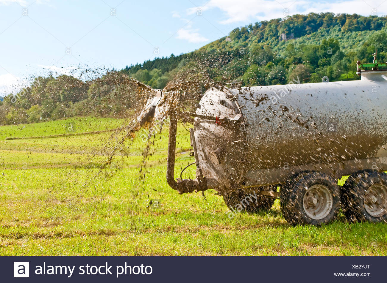 tractor moves manure - Stock Image