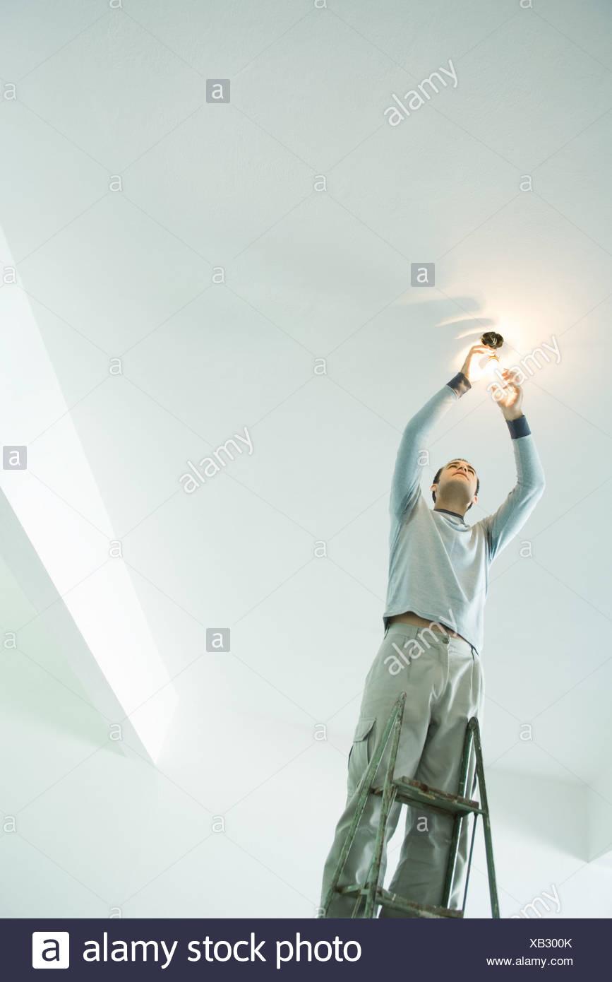 Man changing light bulb - Stock Image