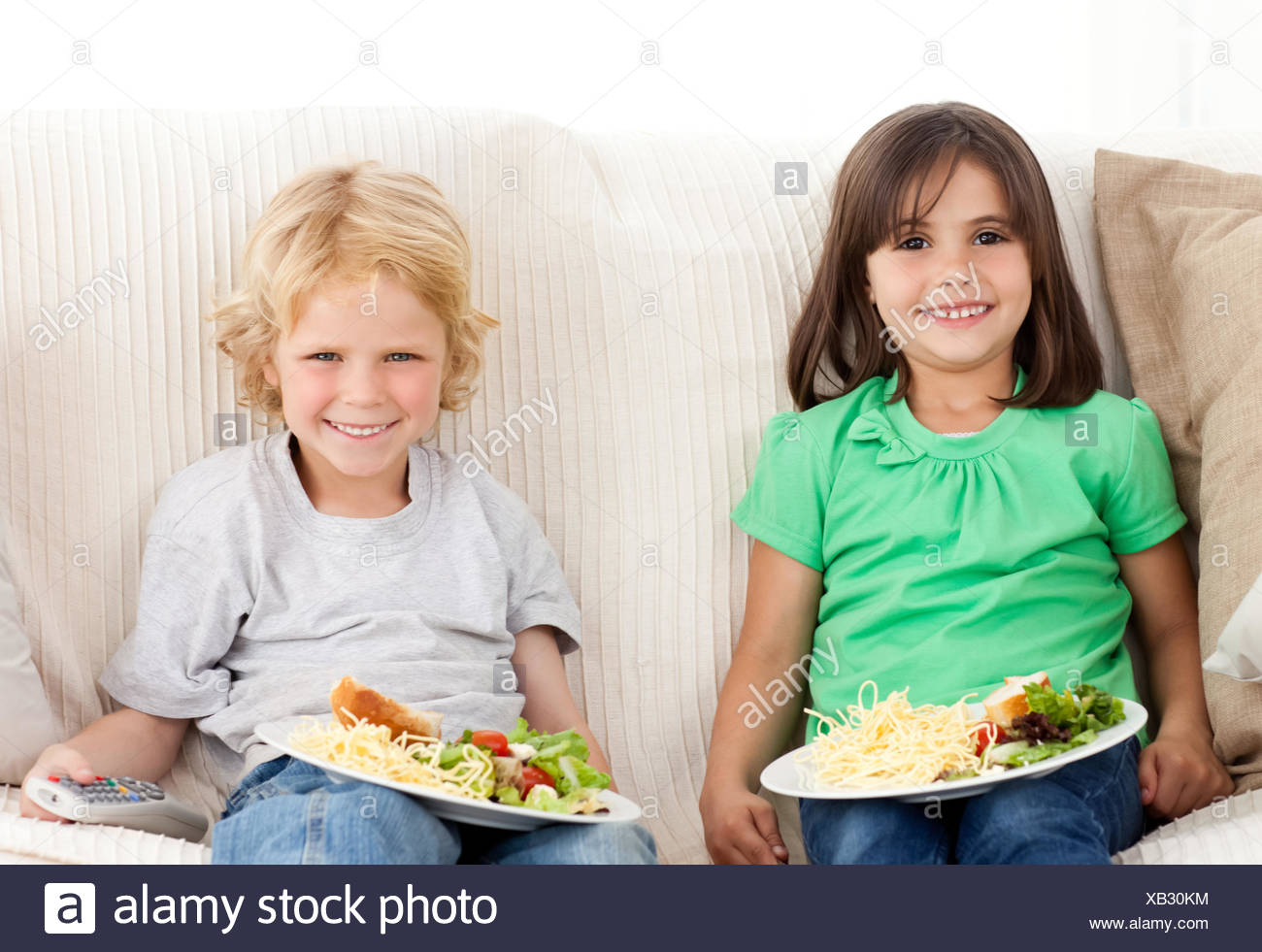Happy brother and sister having TV dinner sitting on the sofa - Stock Image
