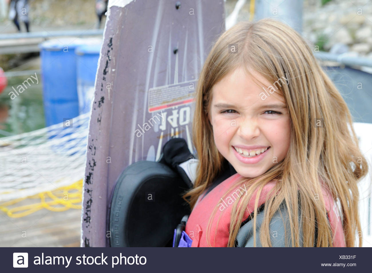 Girl with wakeboard smiles in camera, portrait - Stock Image