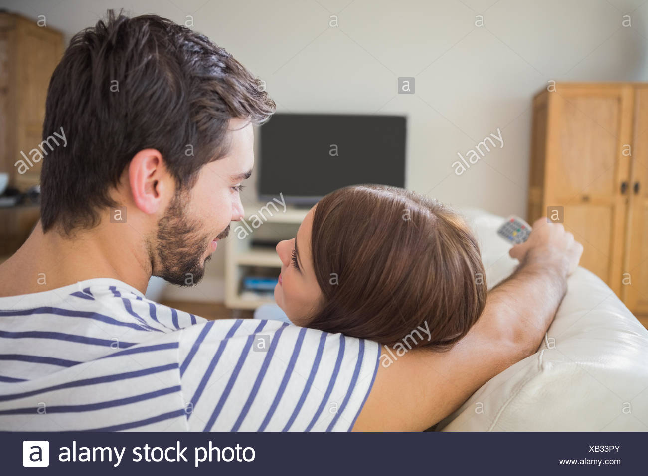 Cute couple watching tv on the couch - Stock Image