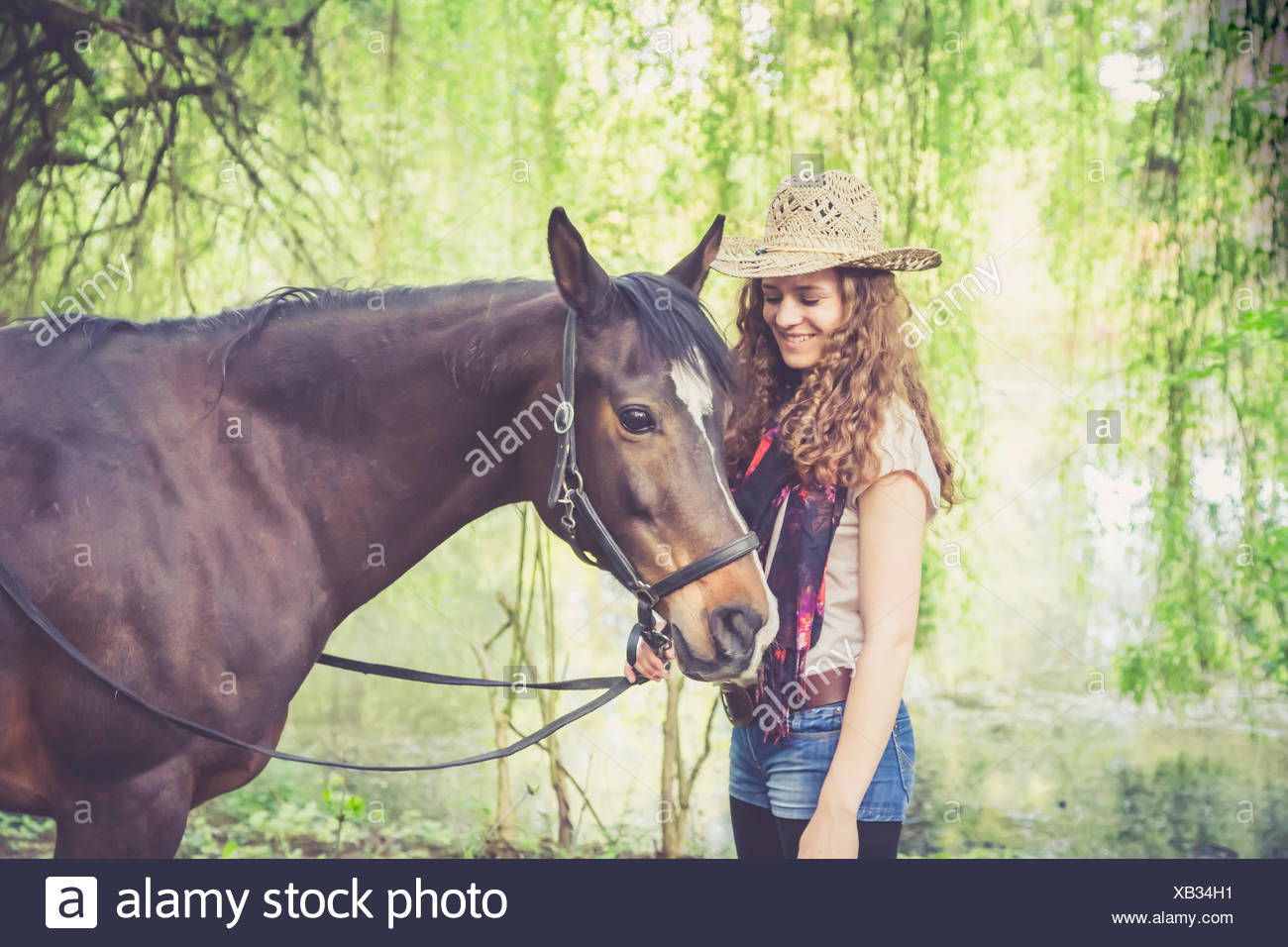 Smiling young woman with Arabian horse - Stock Image