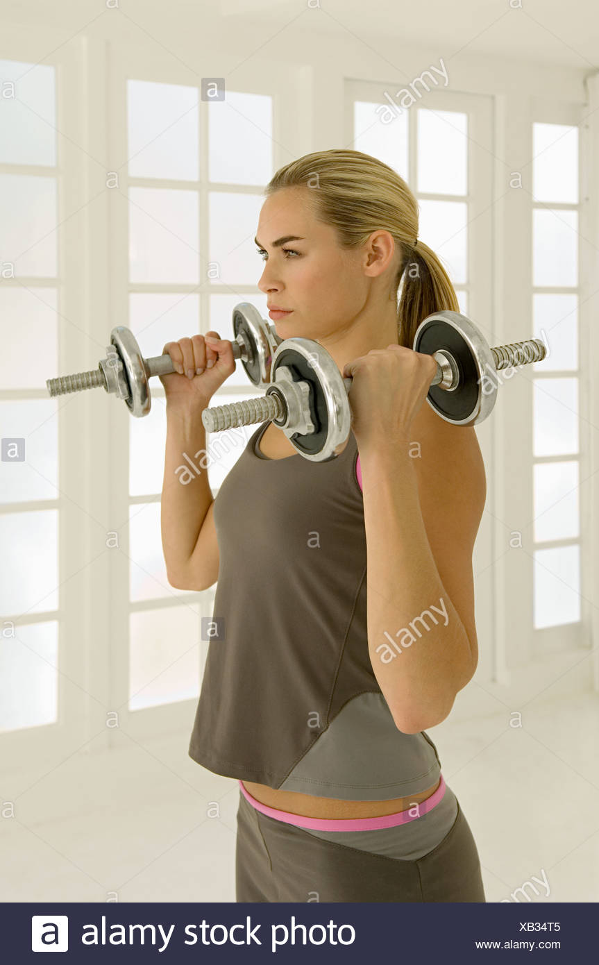Woman using dumbbells - Stock Image