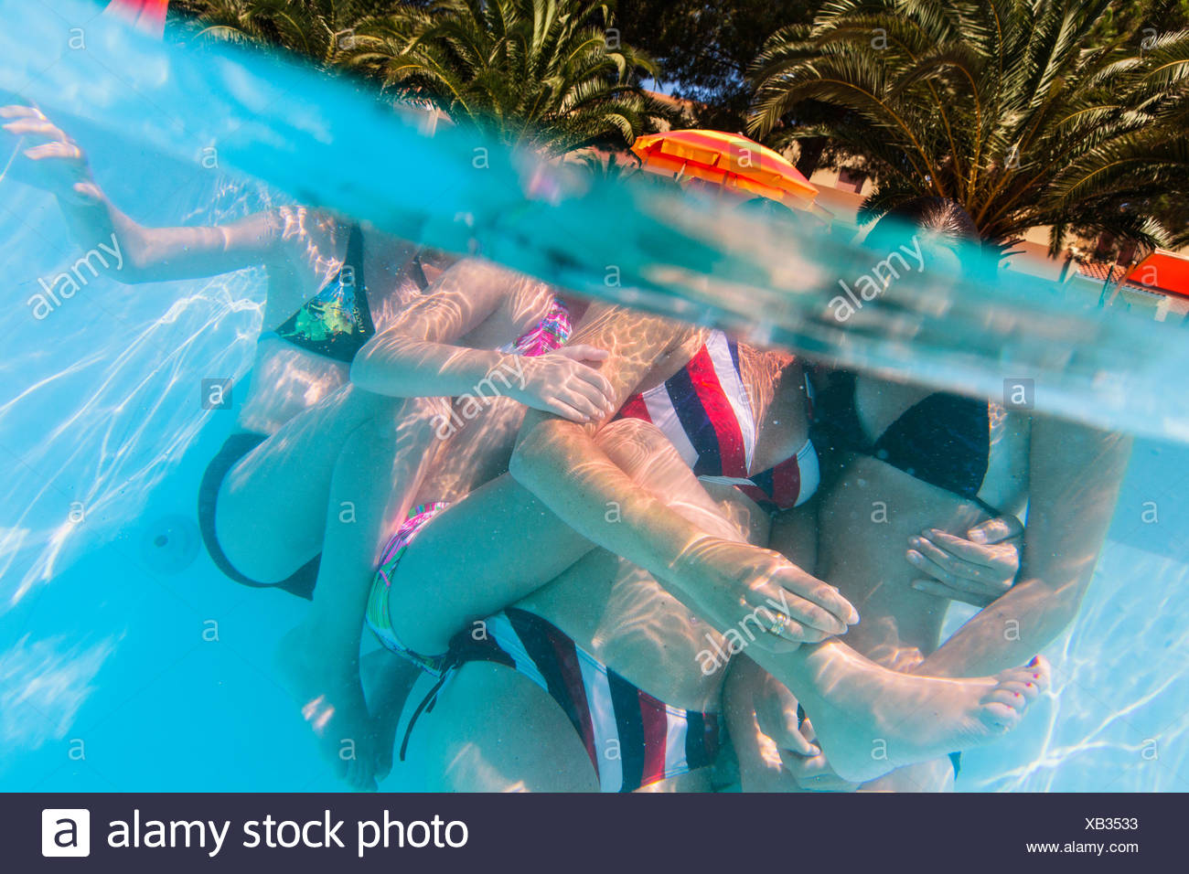 Italy, Sardinia, Alghero, Mother with children (14-15, 16-17) hugging at swimming pool Stock Photo