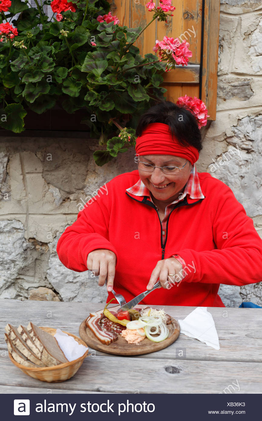 Woman with peasant snack, hearty snack in front of the Koschutahaus mountain lodge, Karawanken, Carinthia, Austria, Europe - Stock Image