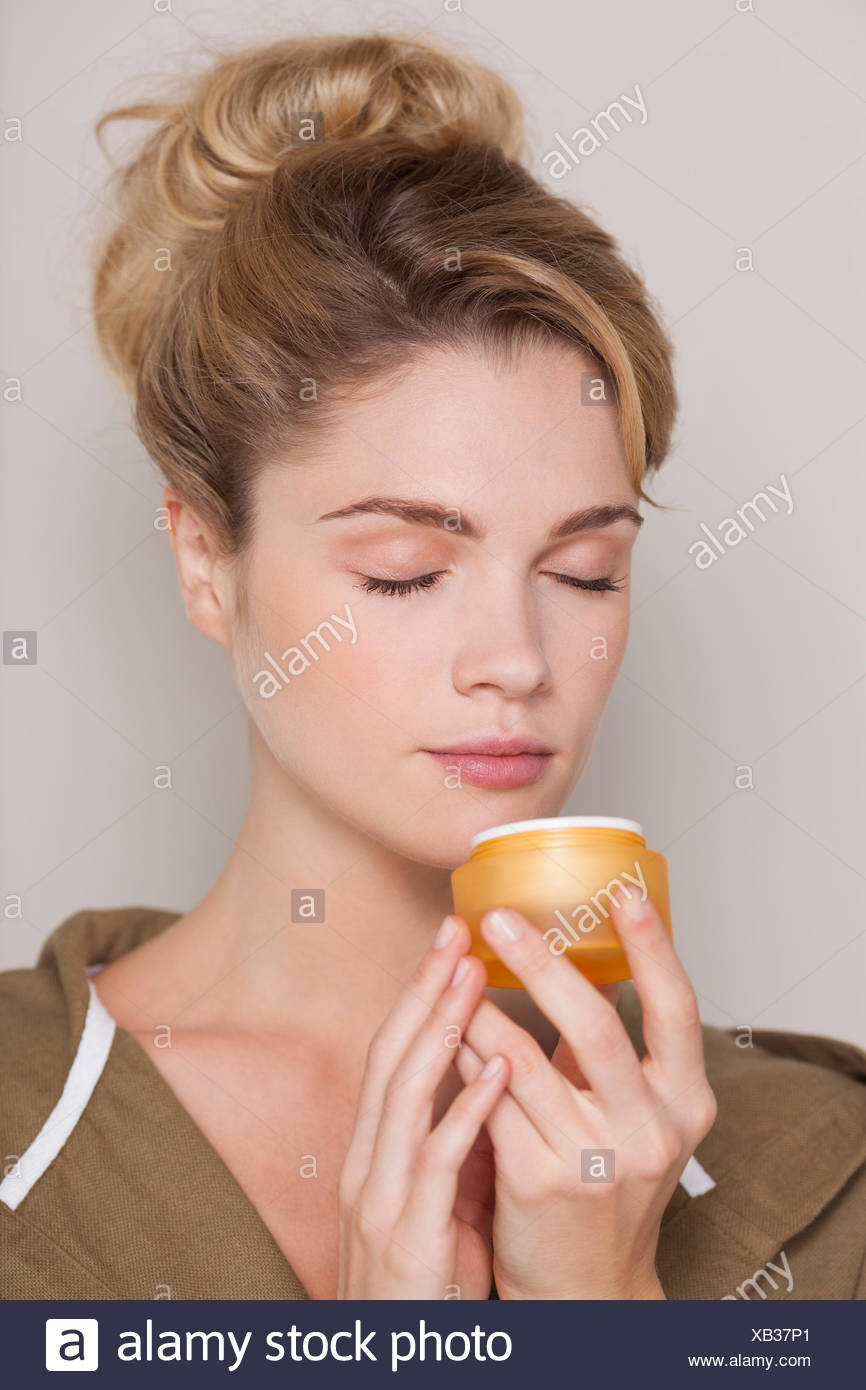 Beautiful woman smelling cream - Stock Image