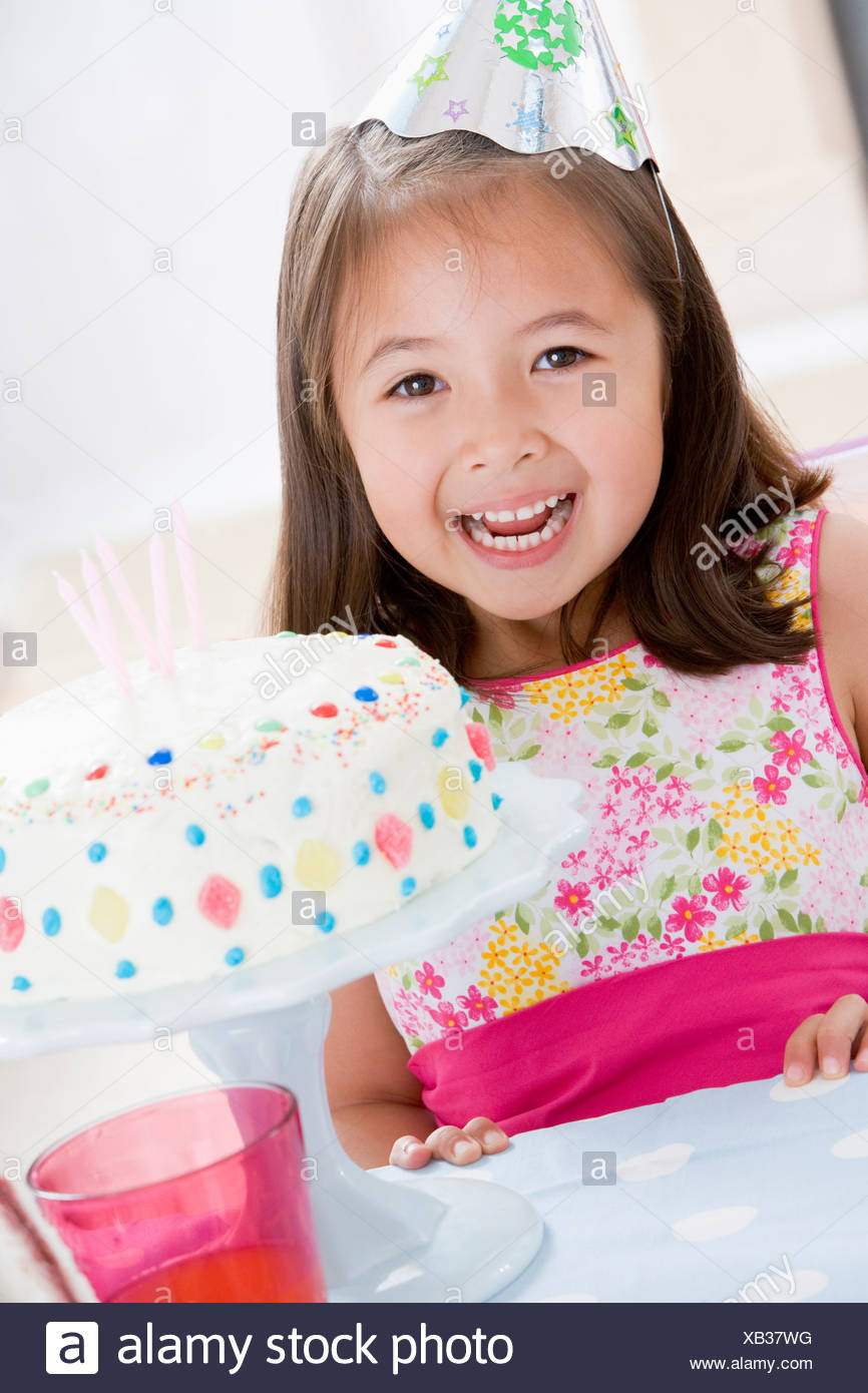 Young girl wearing party hat with birthday cake smiling - Stock Image