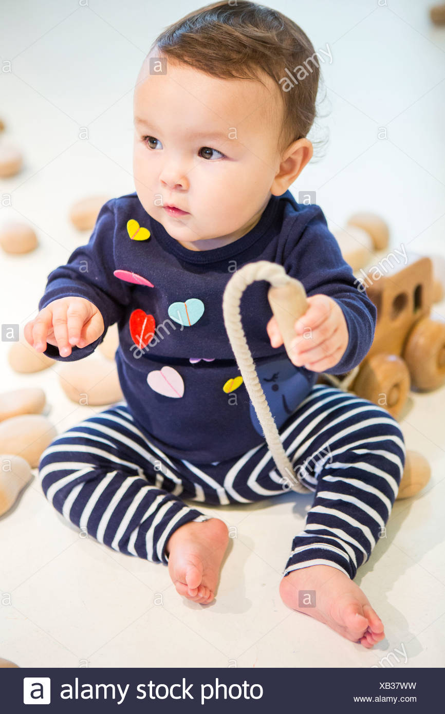 Baby girl sitting on floor with toy - Stock Image
