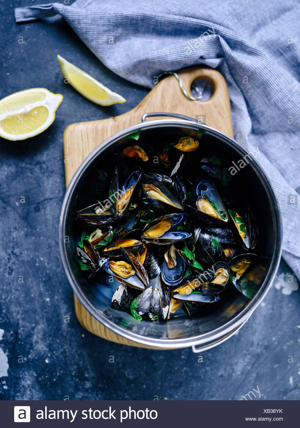 A pot full of cooked blue mussels with parsley and lemon - Stock Image