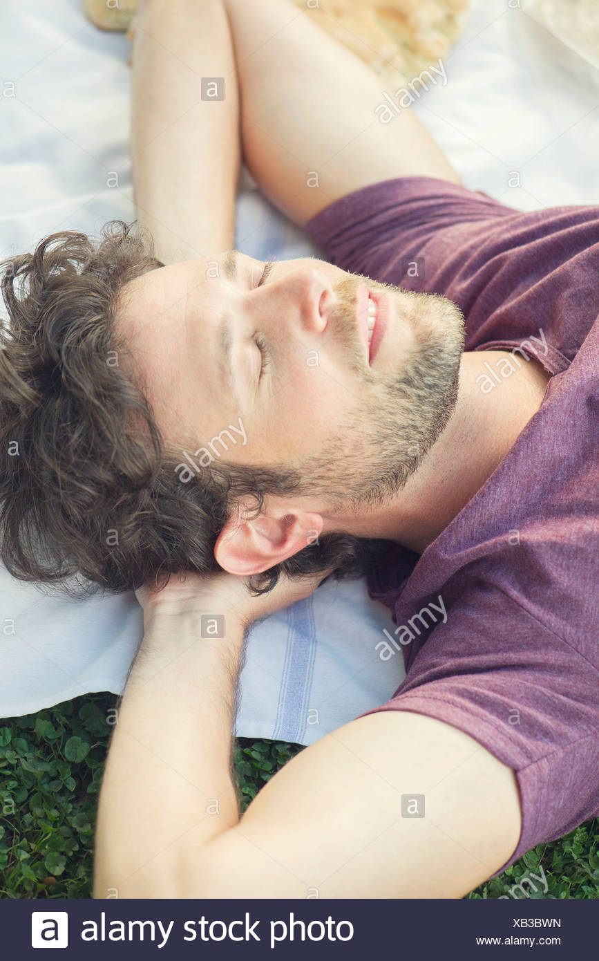 Man napping outdoors - Stock Image