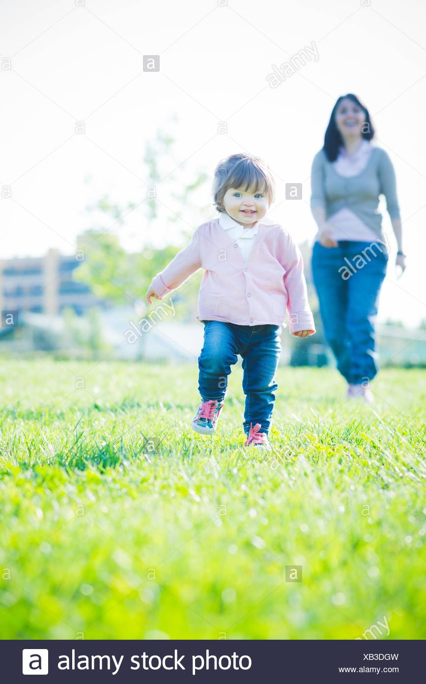 Toddling female toddler in front of mother in park - Stock Image