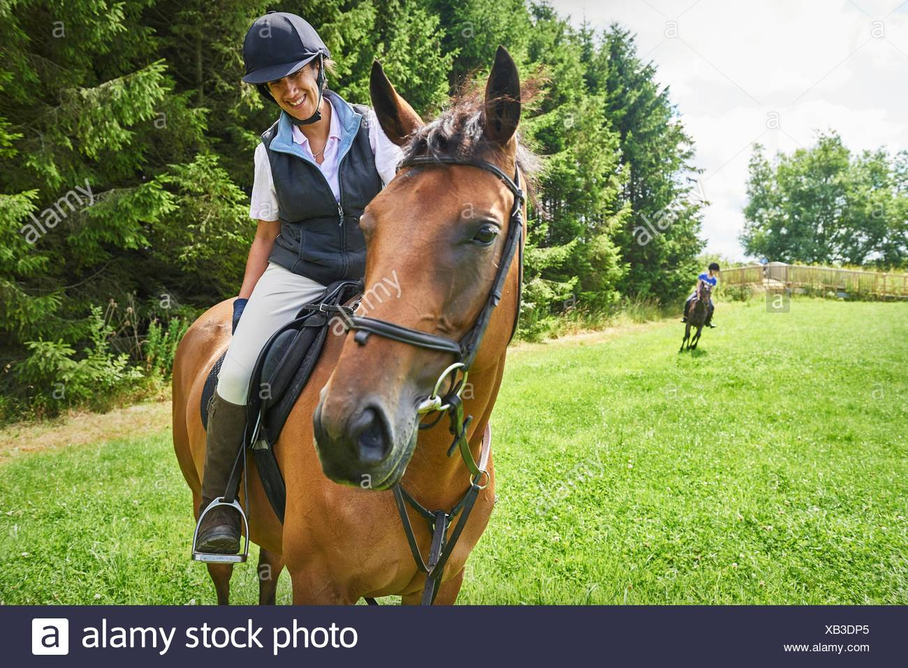 Mature woman on horseback wearing riding hat and boots looking at horse smiling - Stock Image