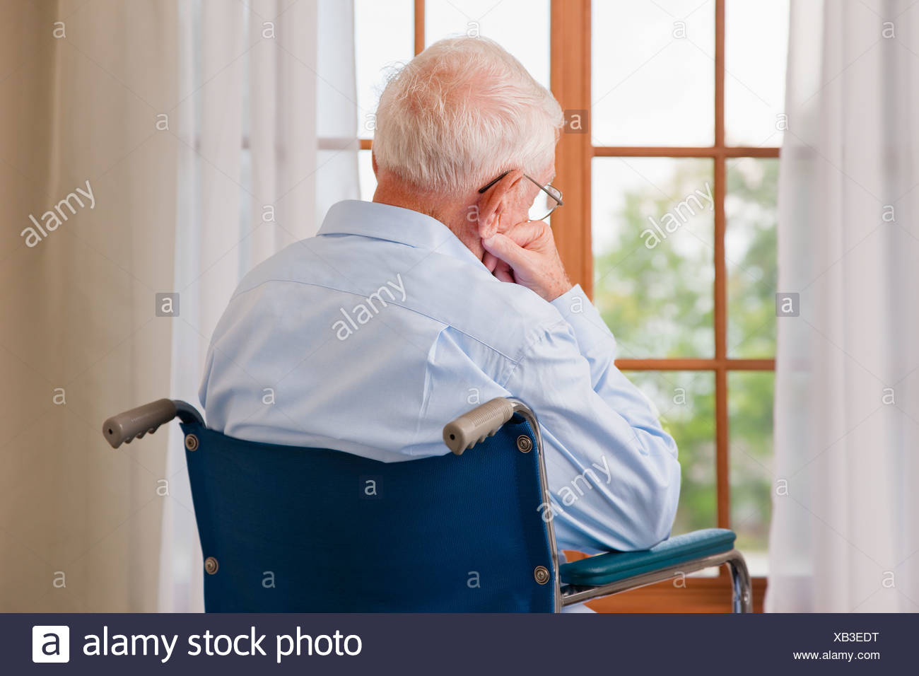 USA, Illinois, Metamora, Rear view of senior man on wheelchair resting in front of window - Stock Image