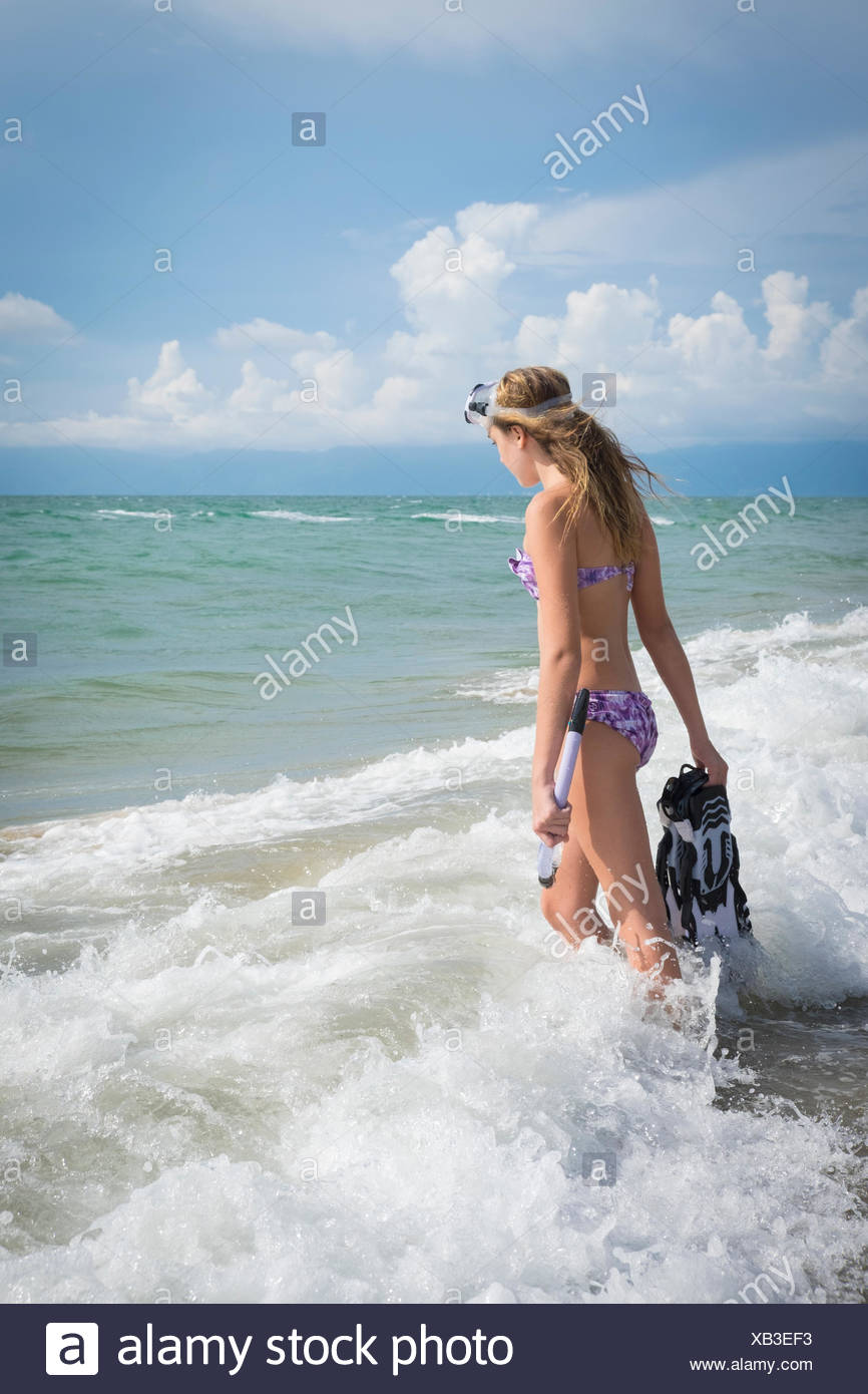 Mexico, Nayarit, teenage girl with snorkel and fins walking into the sea - Stock Image