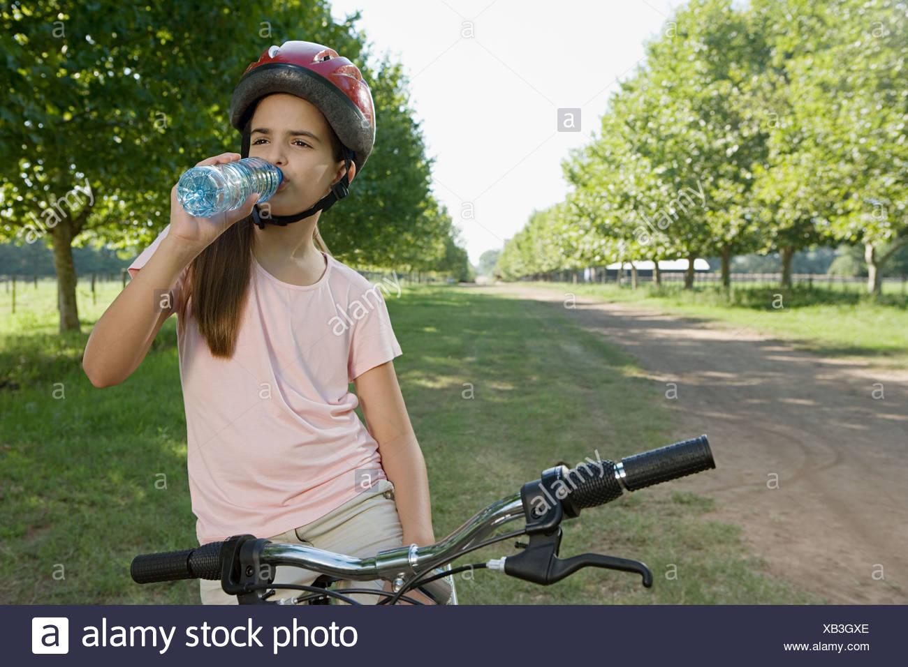 Girl on bike drinking water Stock Photo