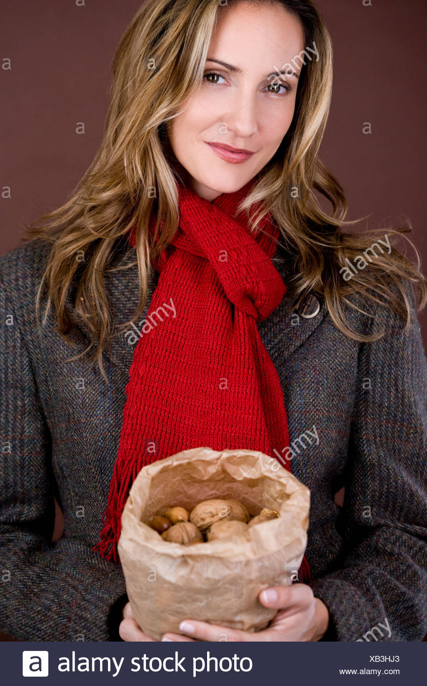 A mid adult woman holding a bag full of mixed nuts - Stock Image