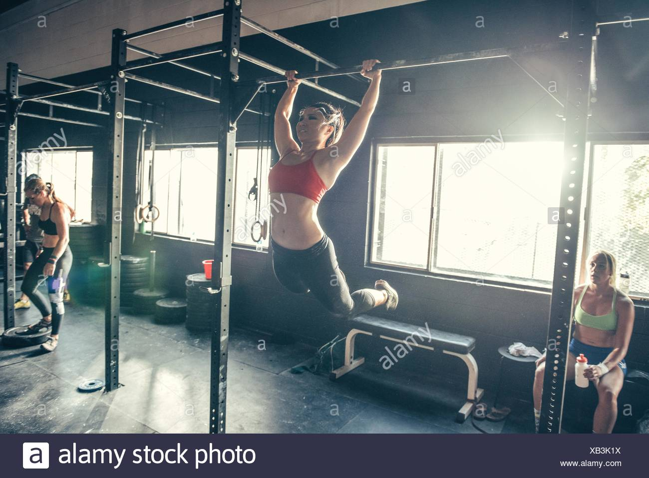 Woman swinging on exercise bar in gym - Stock Image