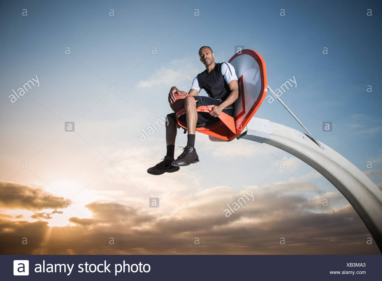 Portrait of a young man sitting in a basketball hoop in a park, Los Angeles, California, USA - Stock Image