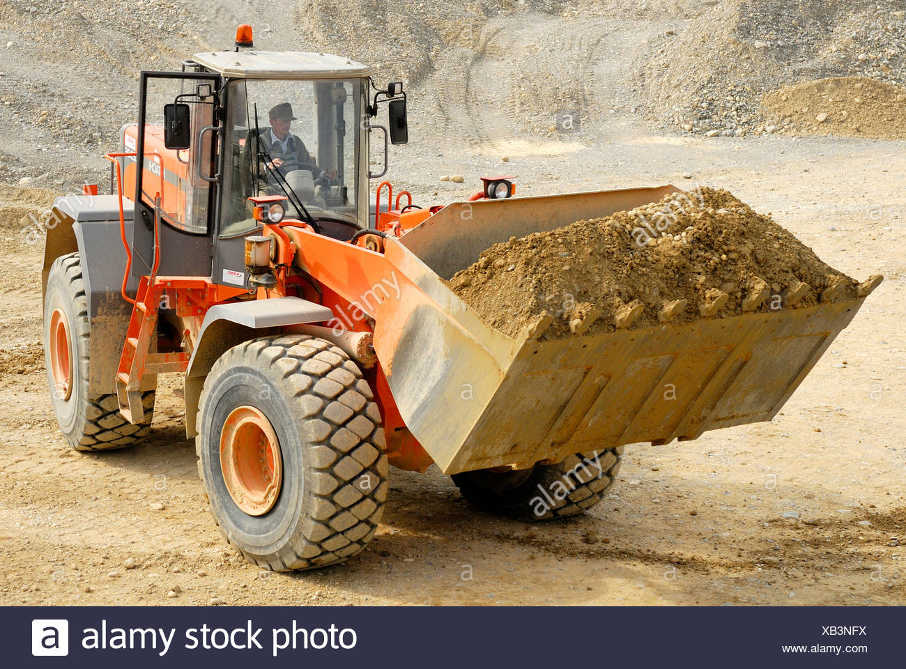 Hitachi LX 290E wheeled loader carrying gravel in a gravel pit - Stock Image