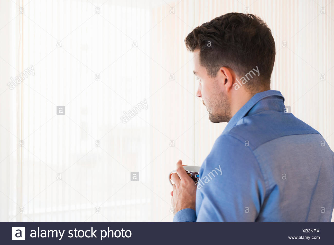 Young man drinking coffee gazing out of living room window - Stock Image