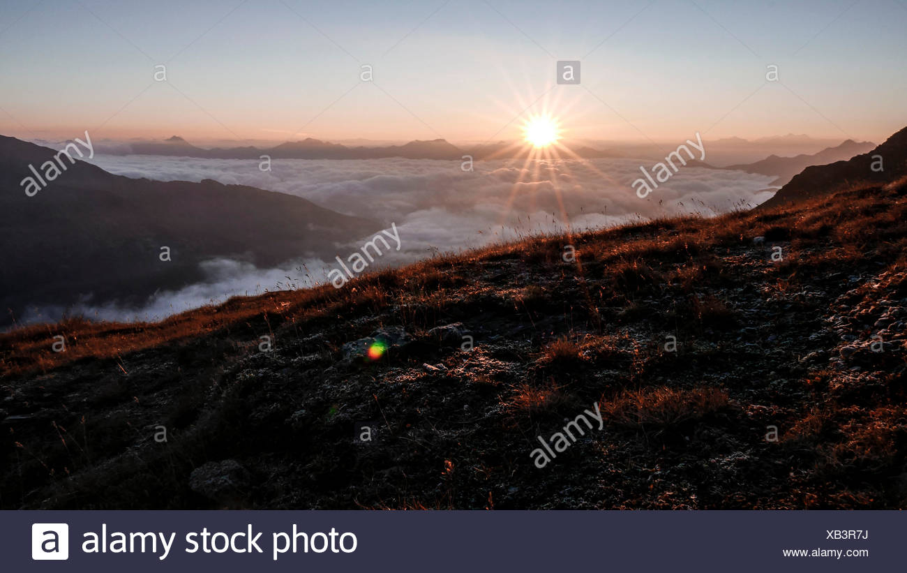 Sunrise above a sea of clouds, view of the Gurgler Kamm above Pfelderer valley and Passeier valley on Sarntaler alps, on the left behind Zillertaler alps, South Tirol - Stock Image