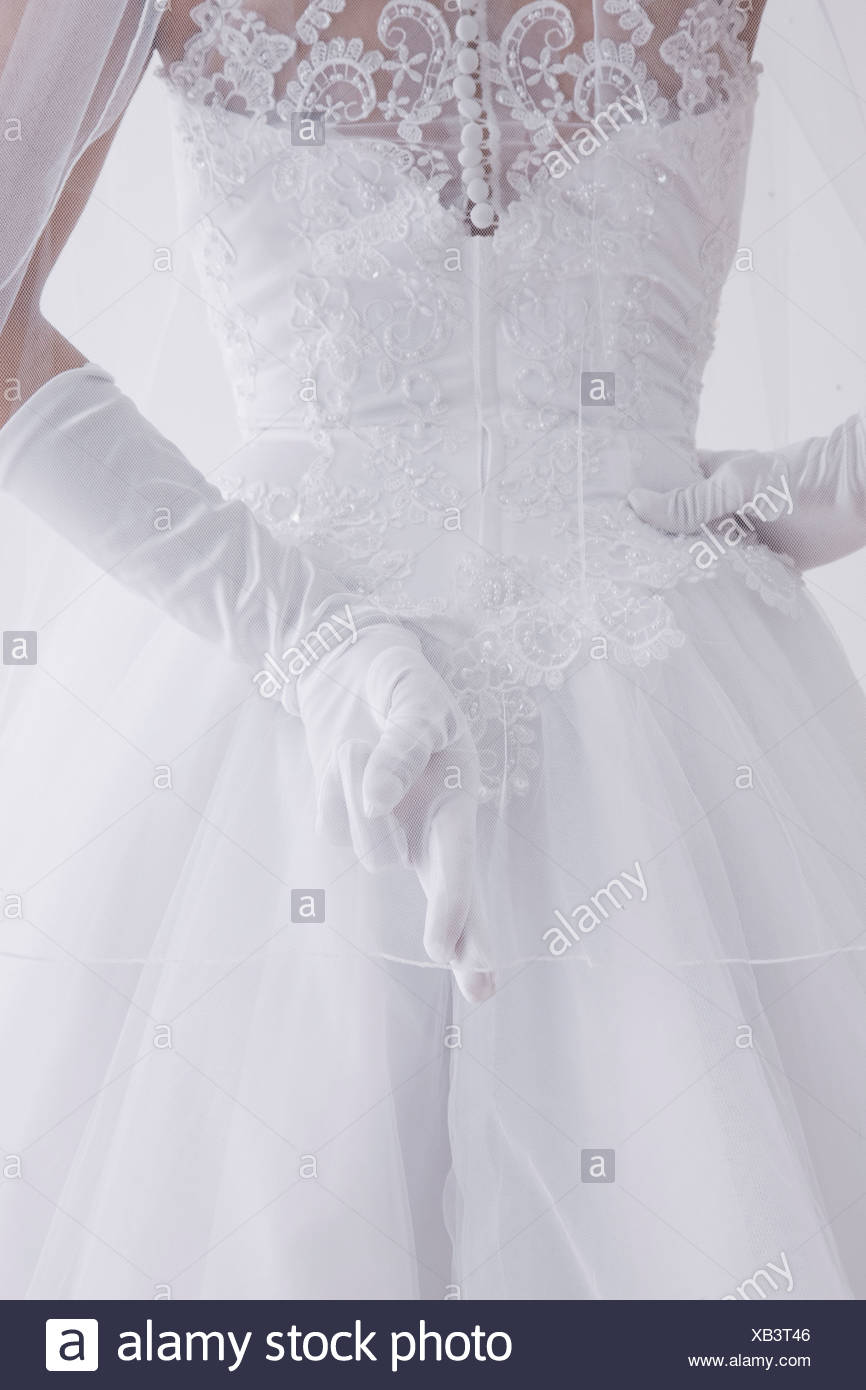 Bride crossing her fingers behind her back - Stock Image