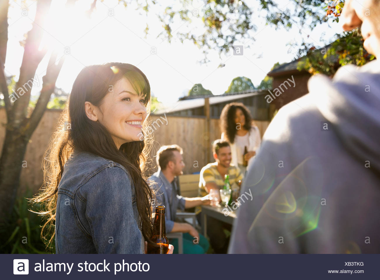 Friends hanging out at backyard barbecue - Stock Image