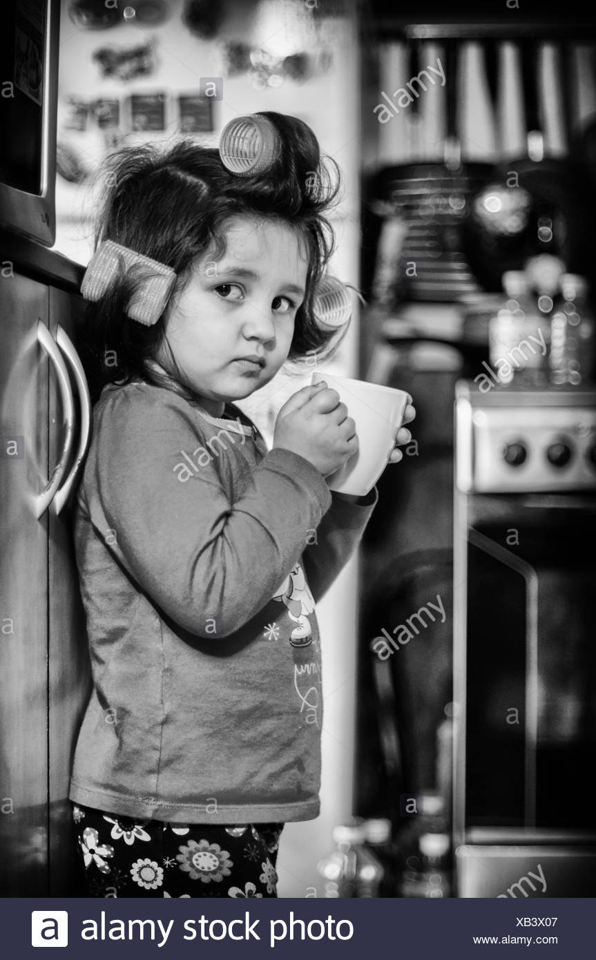 Small girl (4-5) with cup of coffee - Stock Image