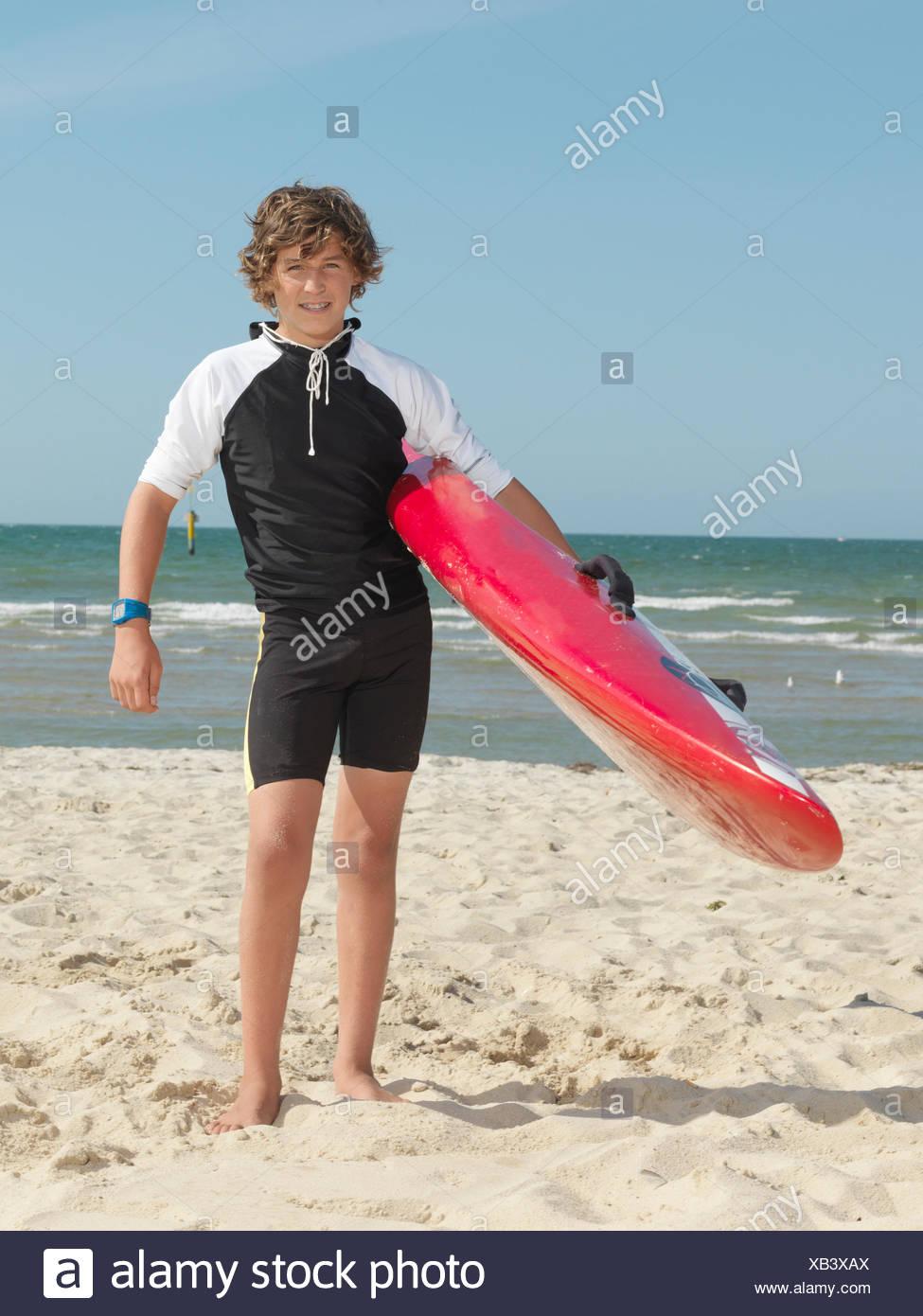 Portrait of teenage boy nipper (child surf life savers) carrying surfboard, Altona, Melbourne, Australia - Stock Image
