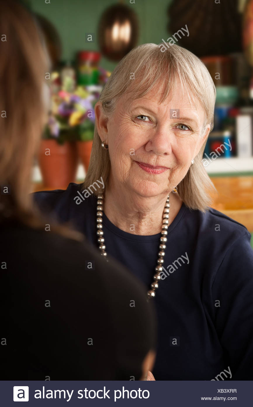 Senior woman in kitchen talking with daughter or friend - Stock Image